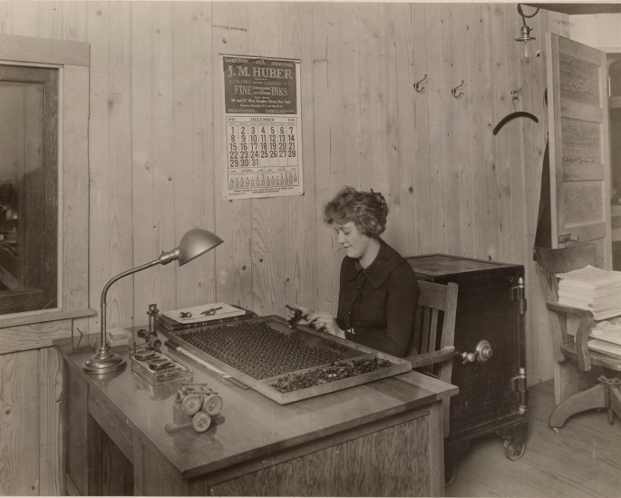 Photo of woman sitting at a desk inspecting gun sights