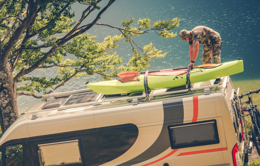 Man putting kayak on an RV roof.
