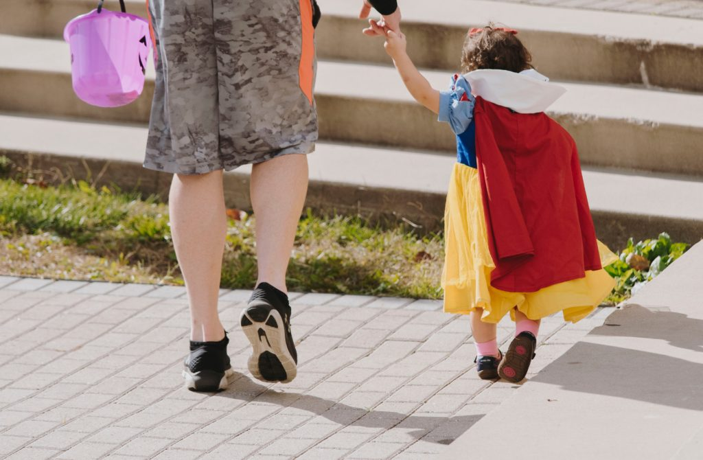 Toddler dressed up as Snow White holding an adults hand.