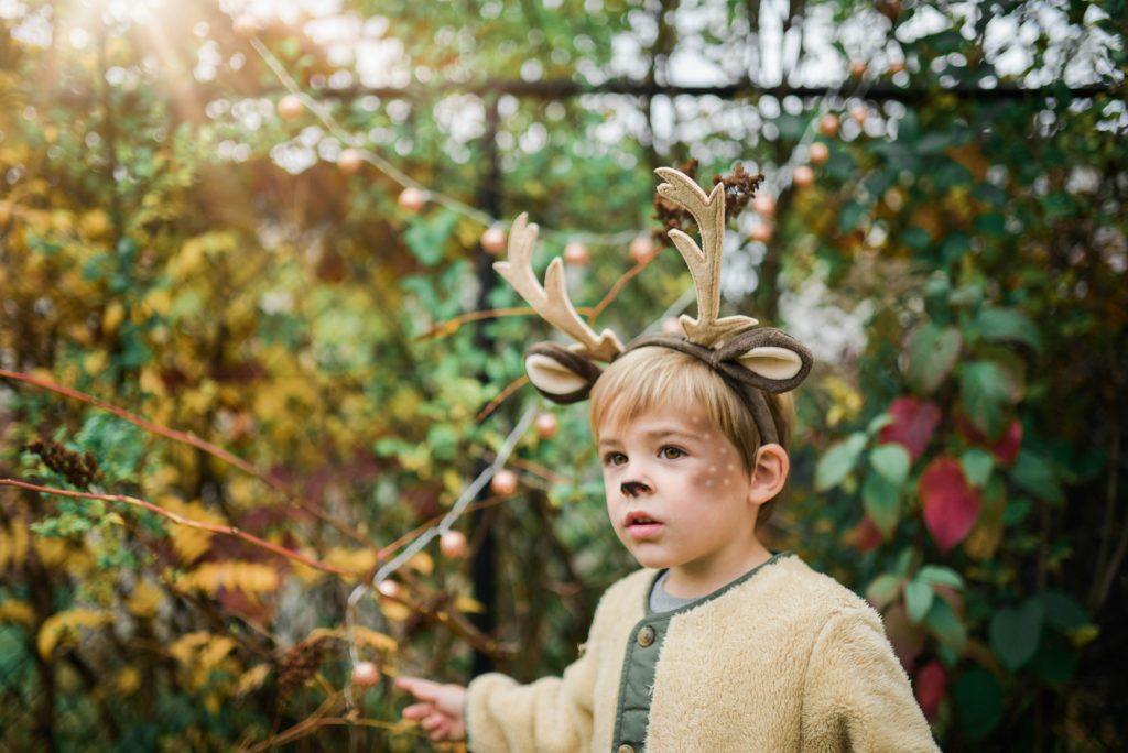 Toddler dressed up as a deer with face makeup to match.