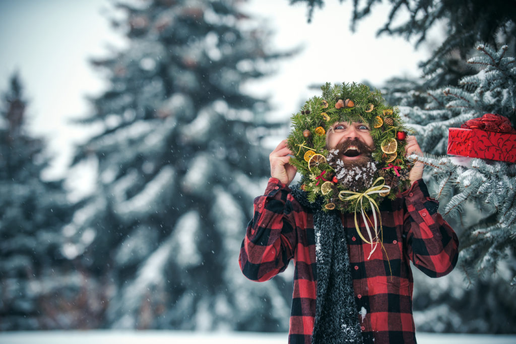 Making new friends on the road are some of the best reasons to go RVing during the holidays! An RV dealer in Utah shows a man holding up a Christmas wreath surrounded by snow.