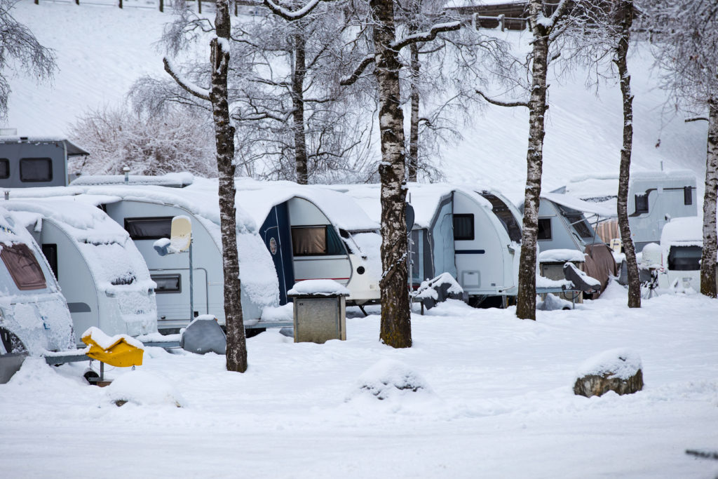 Snow piled up on campers. Winterizing your RV can reduce the risk of conditions like this