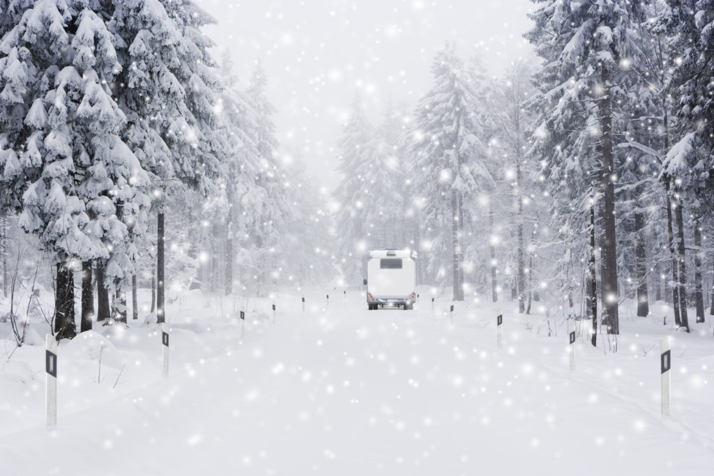 Snowy road with motorhome. Winterize your motorhome to protect it.