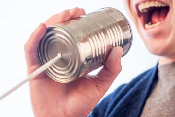 Professional networking - man talking into a tin can on a string