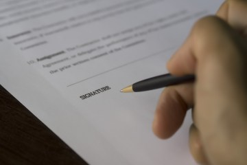 Recent changes in employment law - man's hand ready to sign a contract