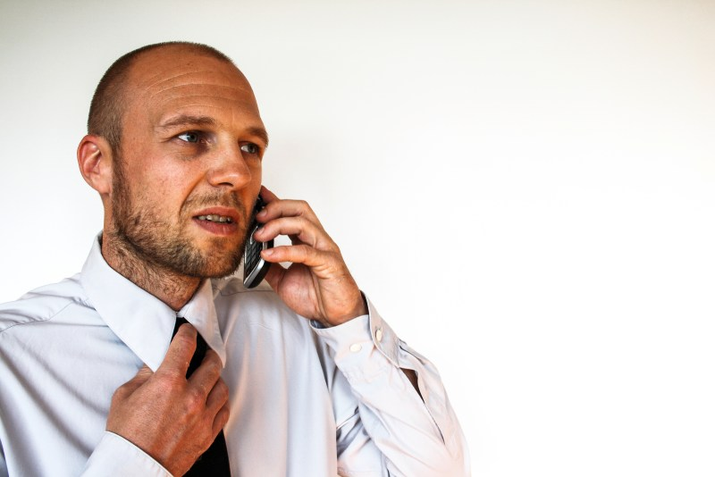 Not getting job interviews - businessman on phone nervously pulling at tie