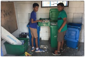 Matisha and Ankit sorting colored paper from non-colored paper. in the recycling room.