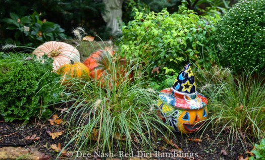 Talavara pottery pumpkin witch in my front flower border.