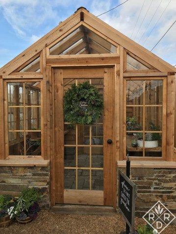Front door of the picturesque greenhouse complete with Christmas wreath.