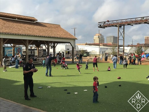 Waco police officer playing ball with children on the lawn at Magnolia Market.