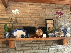 Mantel with orchids, blue and white dishes and Glassybaby candleholders.