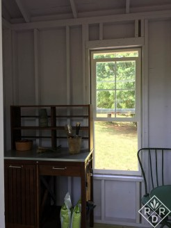Inside is a potting bench and a cafe table and chairs