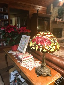 The table behind the sofa has a poinsettia and a Tiffany-style lamp.