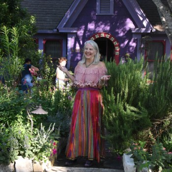 Lucinda Hutson in front of her purple casita and in the middle of her front garden.