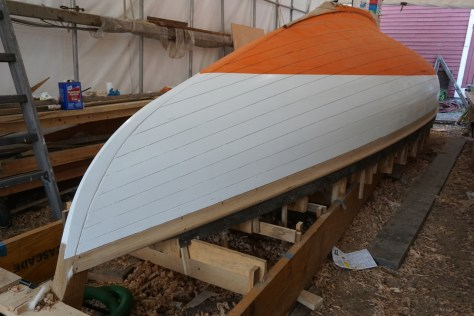 The first coats of primer are applied while the boat is upside down and more accessible.