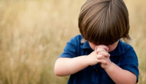 child praying for forgiveness