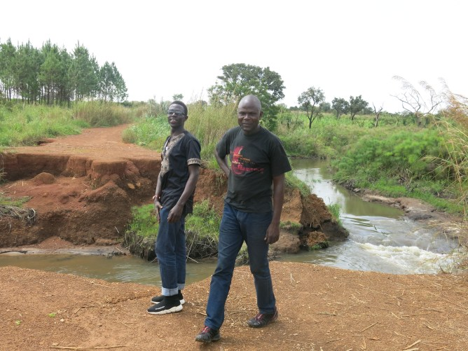 Two men standing near washed out road.