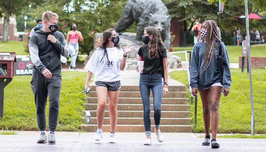 Students walking across campus with masks