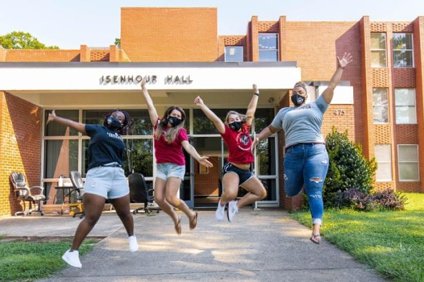 Four students jump for joy in front of residence hall at the start of academic year.