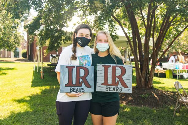 """Two students show """"LR Bears"""" signs they painted"""