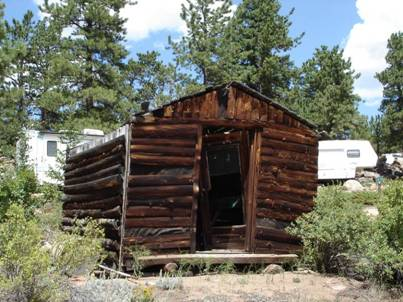 An abandoned log cabin moved to the cabin camp from Deadman, still standing at Alpine Lodge since 1955.