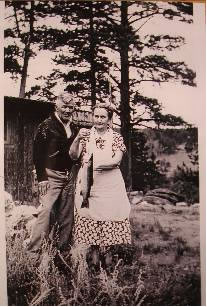 "J.C. and Mary Varner Moore in front of ""Pawnee"" cabin with a nice big ""catch."""