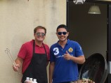 Two men stand grinning next to a barbecue cooking kebabs. One gives a thumbs up, the othe wears an apron and waves a set of barbecue tongs