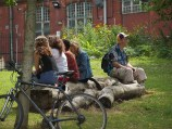 Four women and a man sit on logs at the top of the hill near the community centre. IN the forground a bike leans against a small tree and behind them there are yellow flowers
