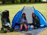 Two women sit under a sunshade enjoying a picnic. There is a pushchair next to them