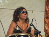 Close up of a woman in blue sunglasses and a gold sequinned top playing drums for the band Baila la Cumbia on the main stage