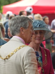 The Lor d Mayor and Lady Mayoress of Bristol enjoy the show. Both are wearing their chains of office and the Lady Mayoress also wears a wide brimmed grey hat with grey flowers.