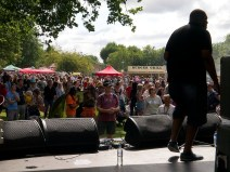 View from the main stage behind a singer, looking out over the crowd who are dancing. There are food stalls in the background
