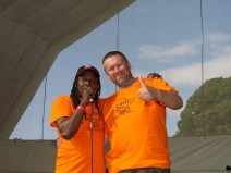 The most generous donor from the festival's crowdfunding campaign gives a thumbs up to the camera as he poses with Julz the main stage compere. They are both wearing bright orange Redfest t shirts and have arms around each other