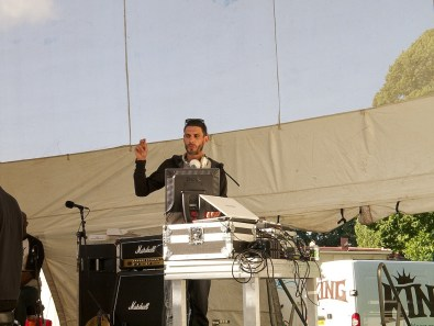A DJ on the main stage clicks his fingers in the air while playing a tune from his laptop
