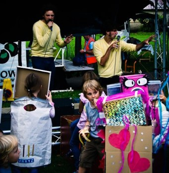 Two men in yellow t shirts entertain a crowd of children dressed in robot costumes made from cardboard boxes. One robot has big girly eyes with long lashes, another is decorated with hearts and ribbons.