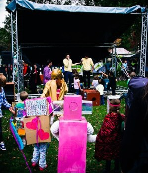 Children in fancy dress watch a show on the stage. The costumes include a pink robot made from cardboard boxes and bendy tubing, and a girl wrapped in red tiger print fur fabric.
