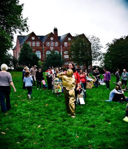 Festival goers stand and sit on a grassy slope. One is dressed as C3PO from Star Wars.