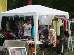 Two ladies laughing on a market stall where they are selling clothes, jewellery and cushions
