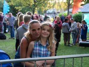 It is dusk after a warm day in the park. A young blonde woman embraces a girl who has flowers in her hair, they are both smiling at the camera while many other people stand behind and chat