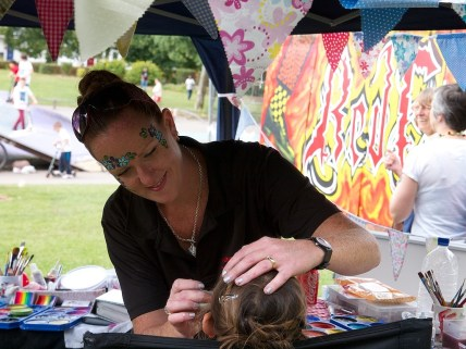 A woman with flowers painted on her face paints a little girl's face on a market stall by the skate park