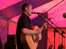 Young man plays an acoustic guitar and sings