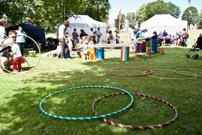 Toddlers play with an installation in the kids area. It's a long tube sitting on top of brightly coloured barrels, and they are watching things emerge from the end of the tube. IN the foreground there are many brightly coloured hula hoops lying on the grass.