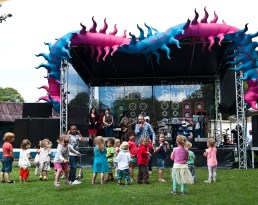 A crowd of toddlers dances to a band performing on the main stage beneath a bright blue and pink spikey inflatable spiral snake