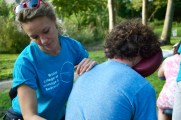 A massage therapist works on the lower back of a seated patient. They are both wearing blue t shirts