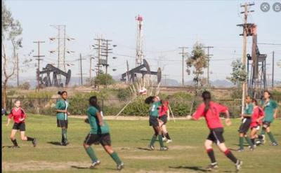 Oil wells in California next to a field where children play. Photo courtesy of Consumer Watchdog.
