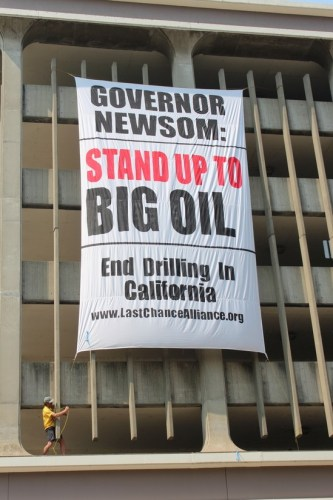 """The filing of the lawsuit took place the day after protesters unfurled a banner proclaiming """"Governor Newsom, Stand Up to Big Oil"""" banner over a building across the street from the State Capitol. Photo by Dan Bacher."""