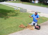 The cable man working on pulling the cable through the tunnel under the driveway