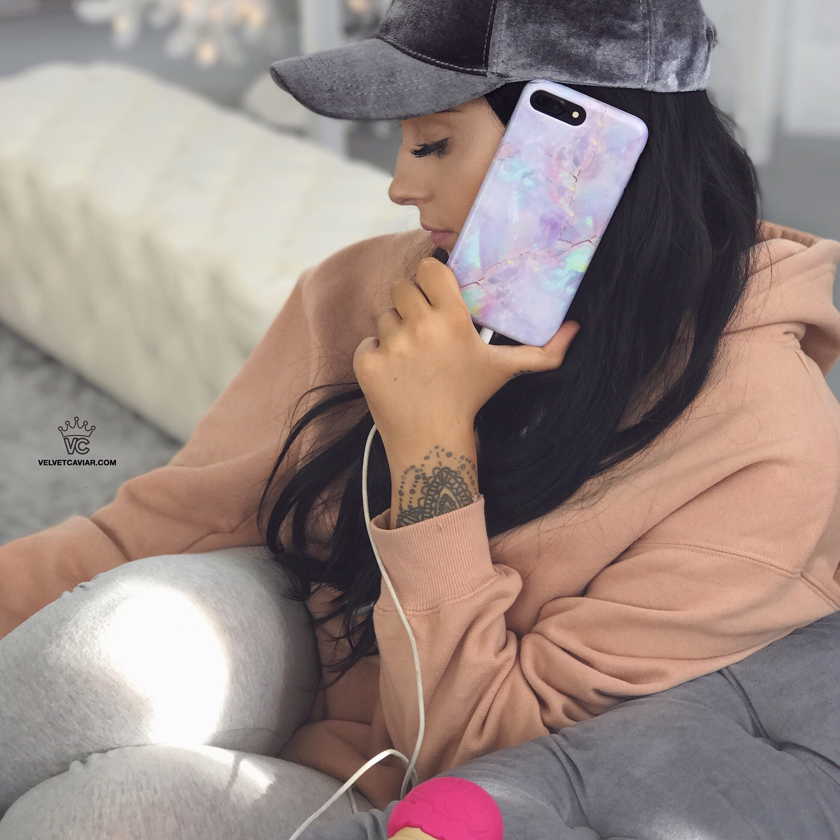a woman sitting in a chair holding phone with glass cover