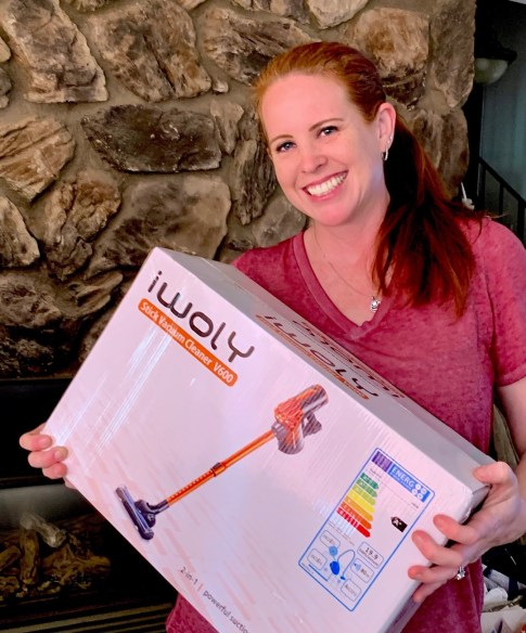 woman holding box with vacuum cleaner