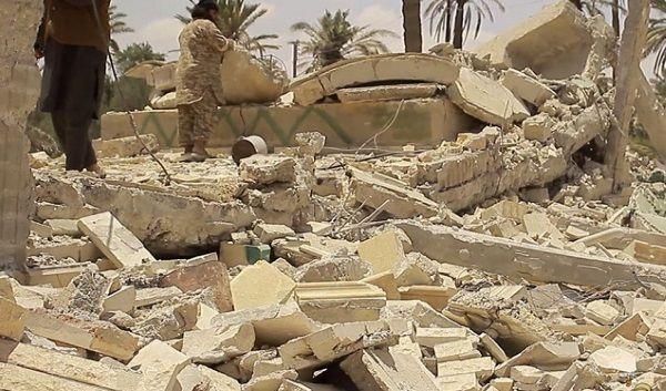 Imagen enviada por los militantes del EI que ya ha sido verificada, en donde se muestran a dos militantes sobre las ruinas de uno de los mausoleos destruidos.